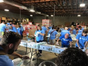Several rows of volunteers sorts through diaper boxes.